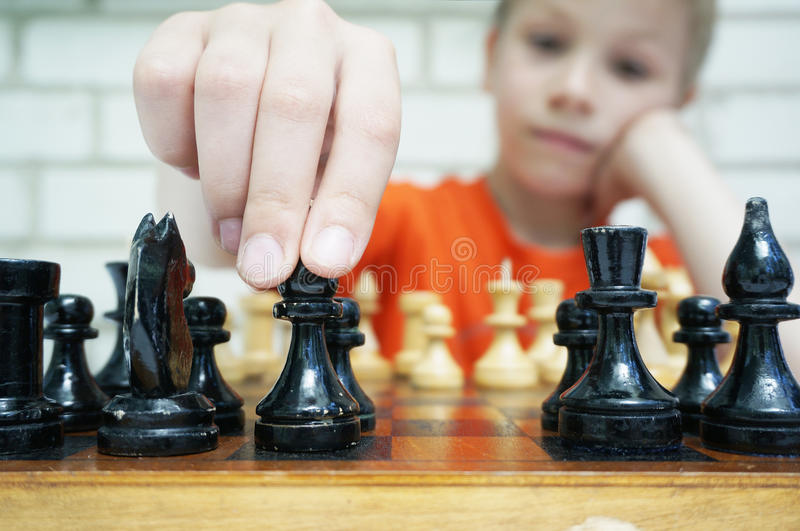 Make a move, boy playing checkmate. Little boy is playing checkmate and making his move royalty free stock photo