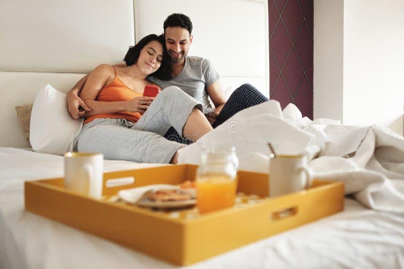 Make och fru som äter frukosten i säng genom att använda telefonen royaltyfri foto