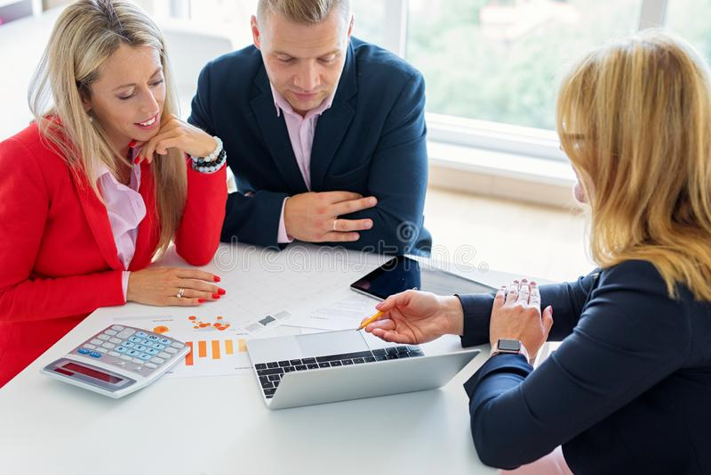 Make och fru som diskuterar investeringsplaner med den finansiella rådgivaren royaltyfria foton