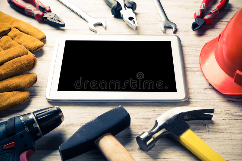 Make online service order. Set of industrial tools and tablet on wooden surface royalty free stock photos