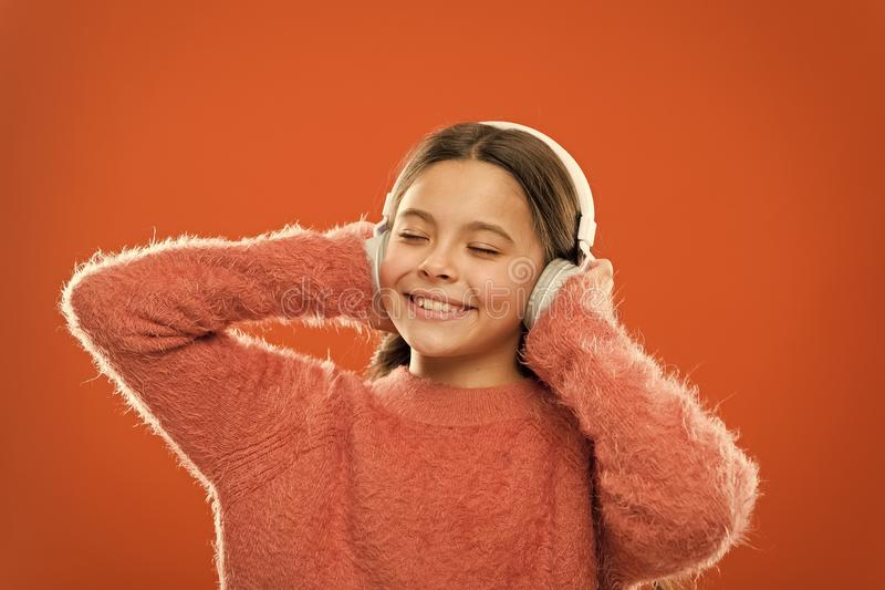 Make outside noise quieter and music sound better. Little girl relaxing with melodious sound. Cute kid listening to. Sound track in headphones. Small child stock photography