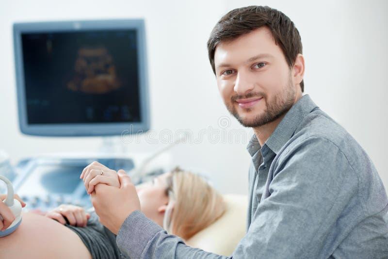 Make som carying om hans gravida fru på diagnostisering i klinik royaltyfria bilder