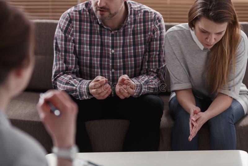 Make som förklarar ett problem till en terapeut medan hans ledsna fru I royaltyfri bild