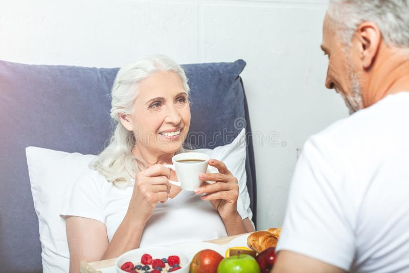 Make som sitter nära kvinnan som dricker kaffe royaltyfri bild