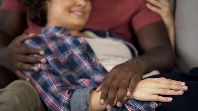 Make som trycker på ömt magen av hans gravida fru, lycklig familj, förväntan arkivbild