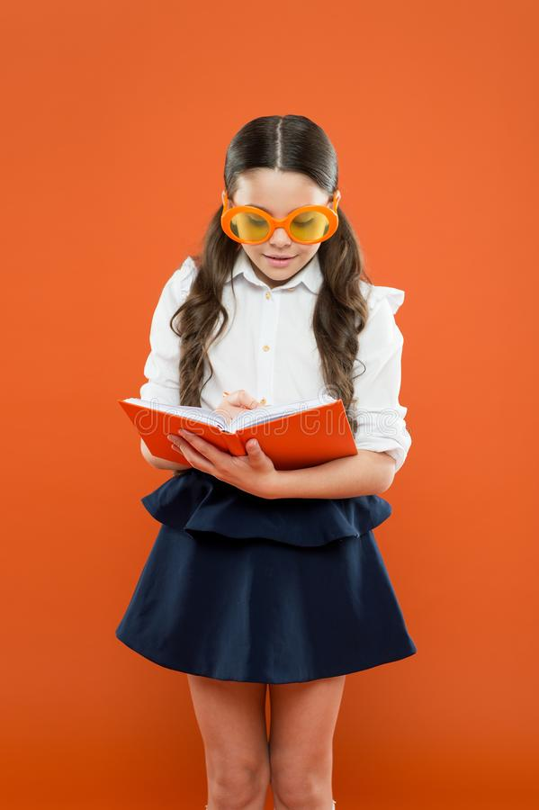 Make some notes. writing in workbook. children literature. get information from book. happy school girl in uniform and. Party glasses. small child with notebook stock image
