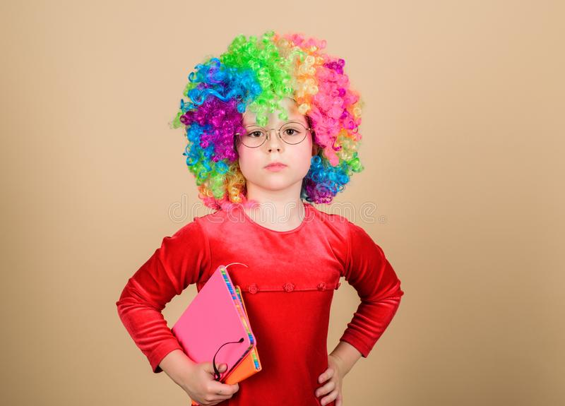 Make studying fun. Truly happy childhood. Girl cute playful child wear curly rainbow wig. Life is fun. Happy little. Child girl. International childrens day royalty free stock image