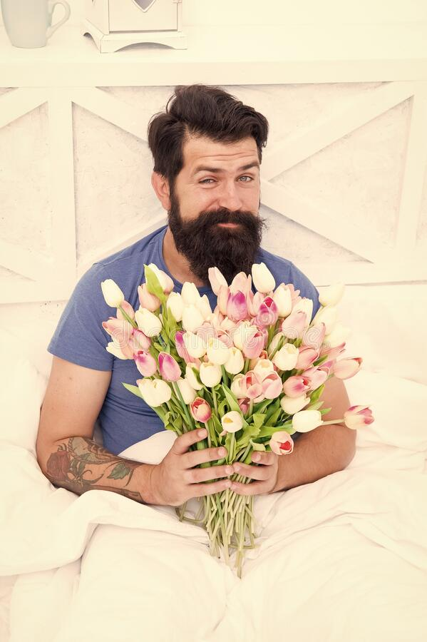 Make surprise concept. Gift for spouse. Bearded hipster in bed. Spring in bedroom. Man hold tulips bouquet while. Relaxing in bed. Fresh flowers. Flowers stock images