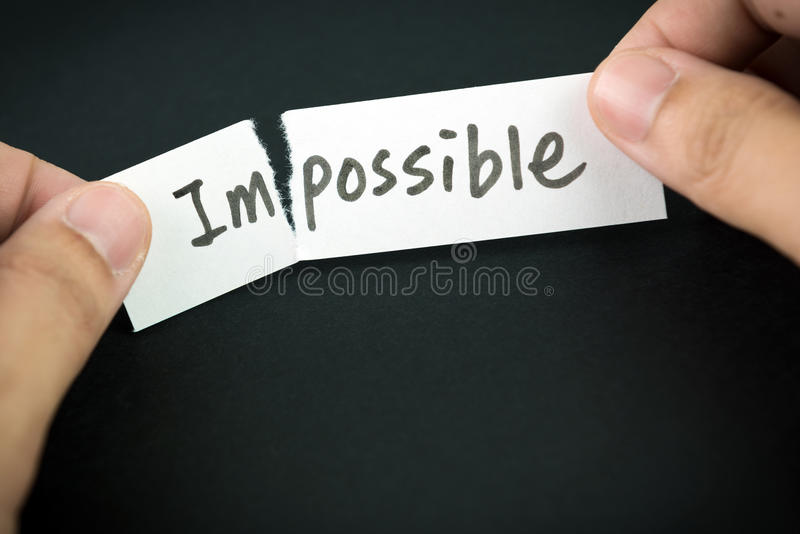 Make thing possible. Tearing the word impossible on paper to possible stock images