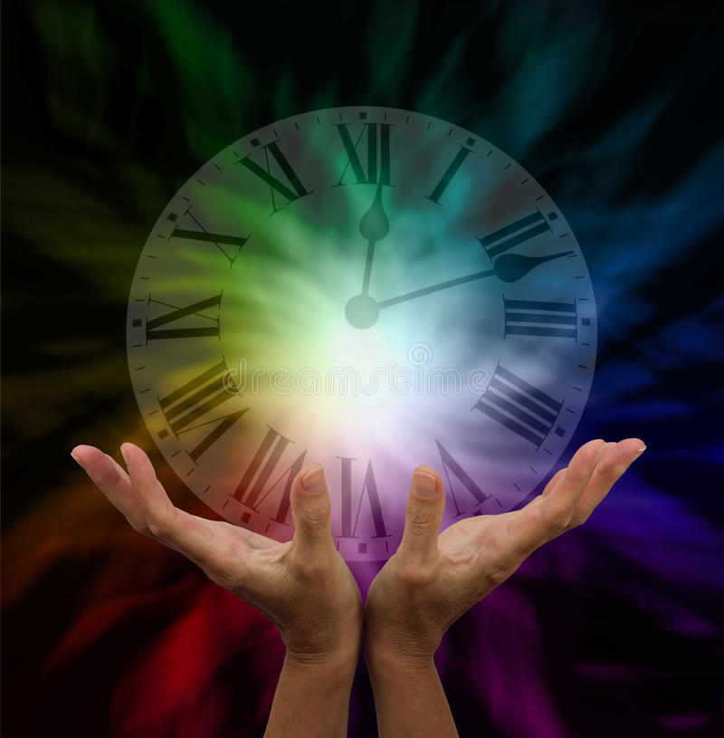 Make Time for Healing. Healer's hands out stretched with transparent clock face hovering above and a dark rainbow energy background stock photo