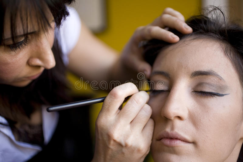 Make Up Applied. Young attractive model getting her face make up applied for a fashion photoshoot royalty free stock photos