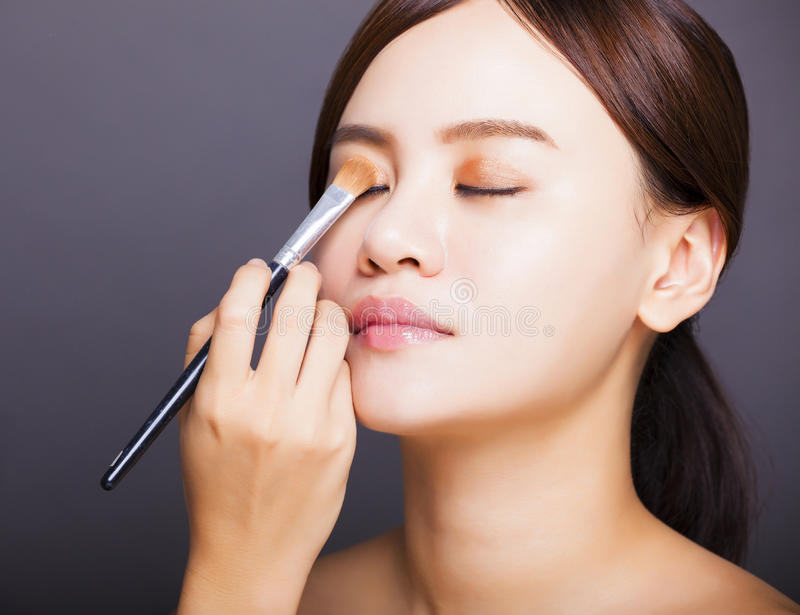 Make up artist applying color eyeshadow on model's eye. Isolated on gray background royalty free stock images