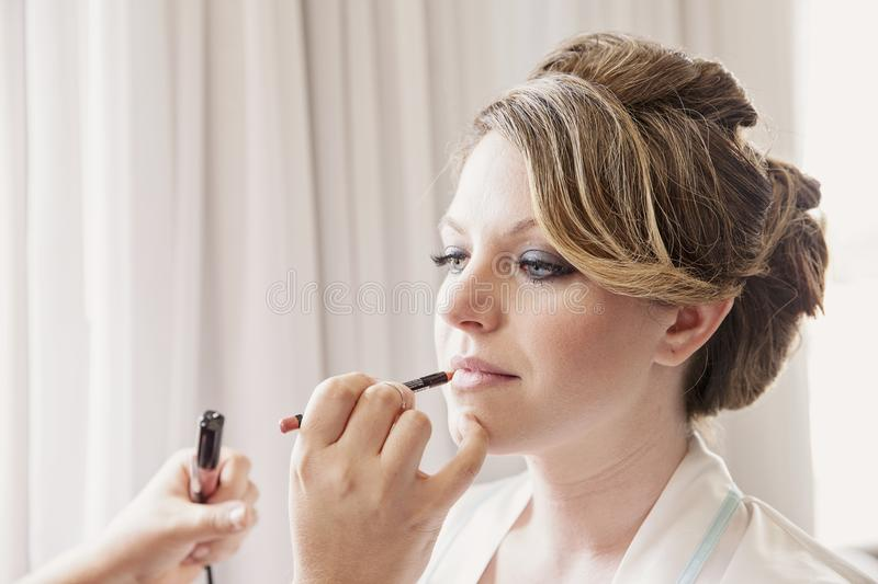 Make up artist applying lipstick. Hand of make-up artist applying lipstick to face of bride stock photo