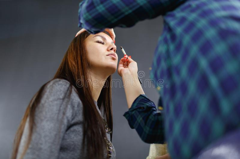 The make-up artist is applying makeup to the young girl. stock photo