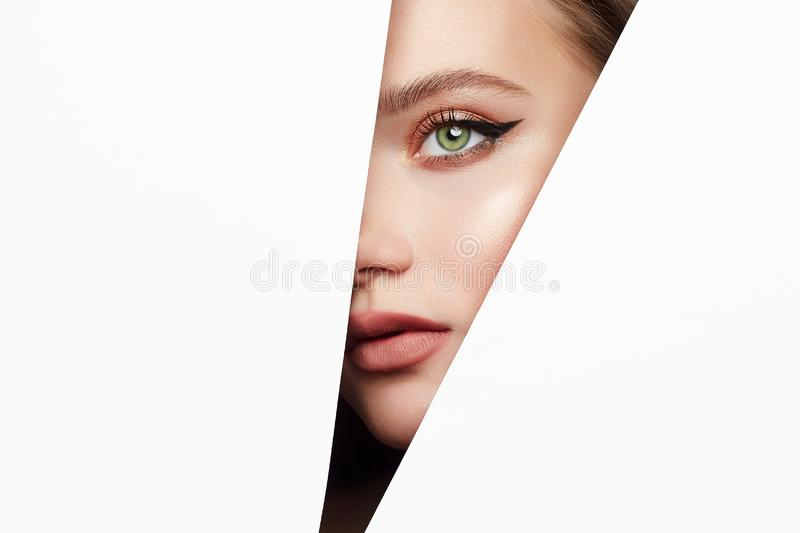 Make-up artist concept. arrows on the eyes. Young beautiful woman with makeup into paper hole. make-up artist concept. arrows on the eyes stock photos