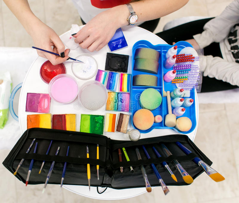 Make-up artist does a face painting to the child. Makeup cosmetics and other essentials on artistic background top view. stock photos