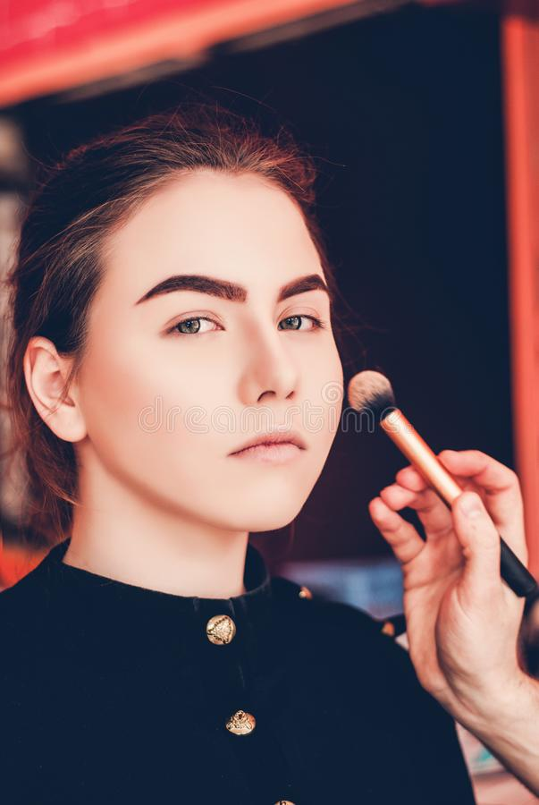 Make-up artist doing make-up of a beautiful young girl in the studio royalty free stock image