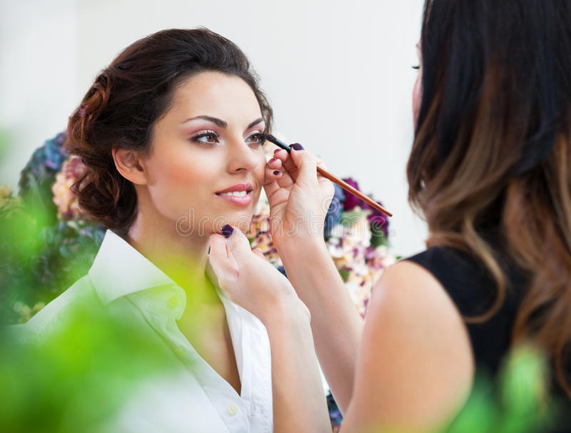 Make-up artist doing make up for young beautiful bride stock images