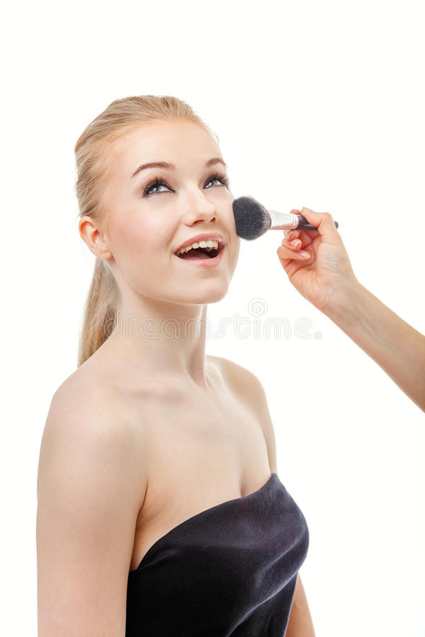 Make up artist doing professional make up of young woman stock images