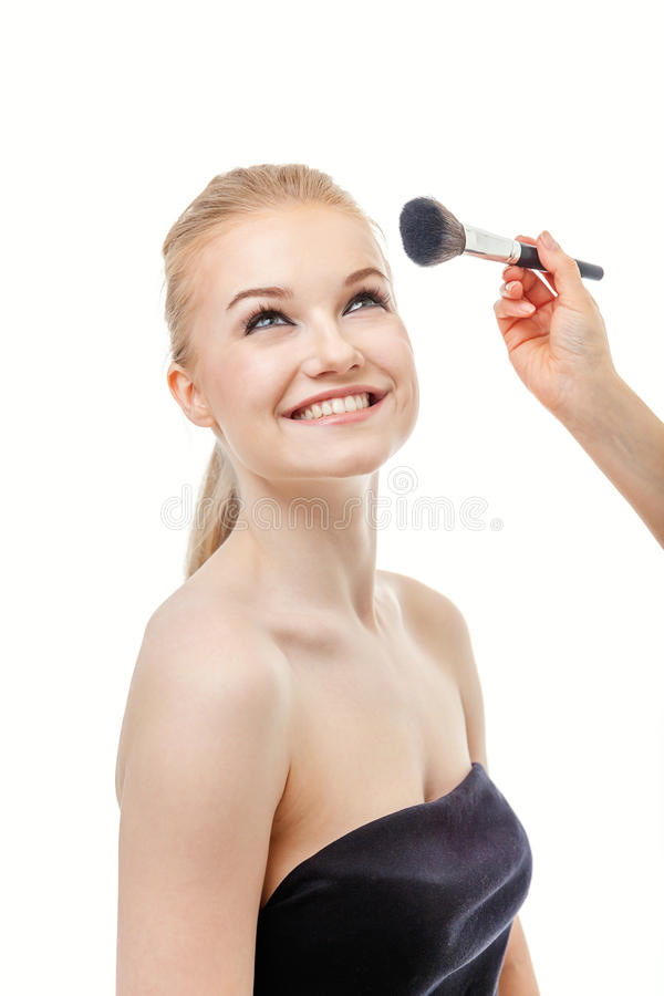 Make up artist doing professional make up of young woman royalty free stock photos