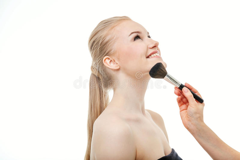 Make up artist doing professional make up of young woman royalty free stock photo