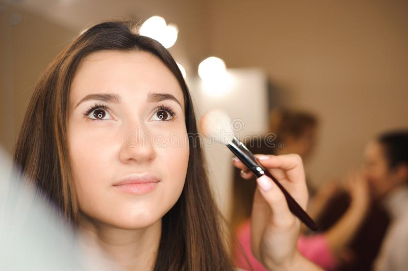 Make up artist doing professional make up of young woman. Beauty shcool stock photo