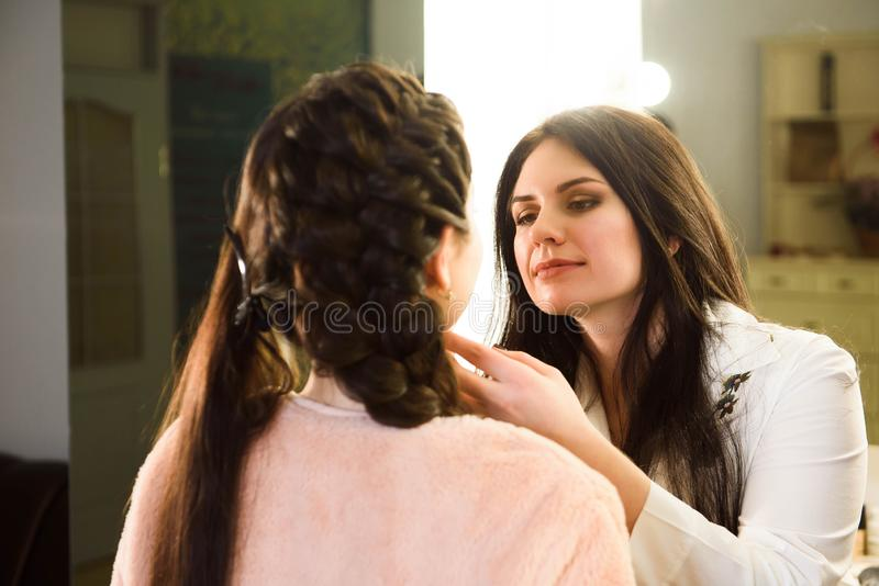 Make up artist doing professional make up of young woman. School of make-up artists. royalty free stock photo