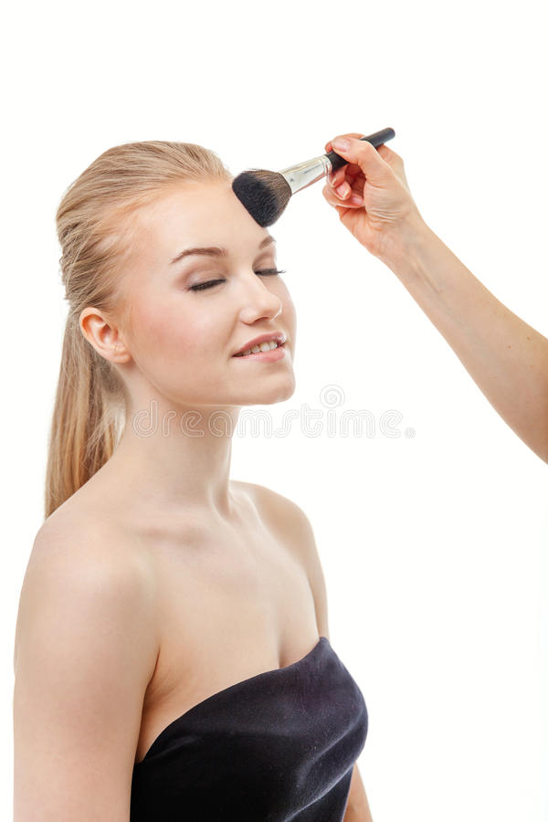 Make up artist doing professional make up of young woman royalty free stock photography