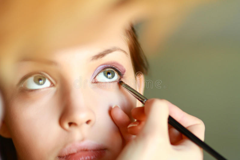 Make up artist doing professional makeup of young woman royalty free stock photo