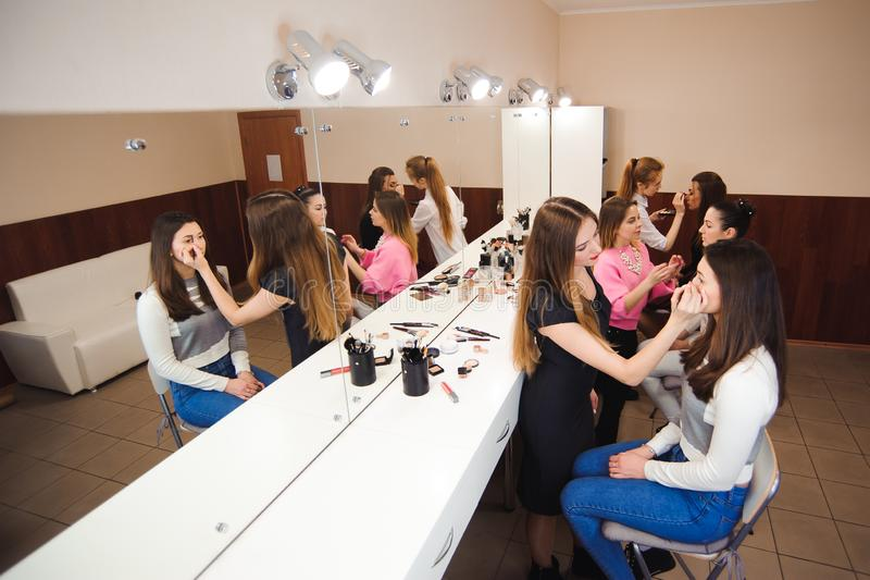 Make-up artist doing professional make-up of young woman royalty free stock photography