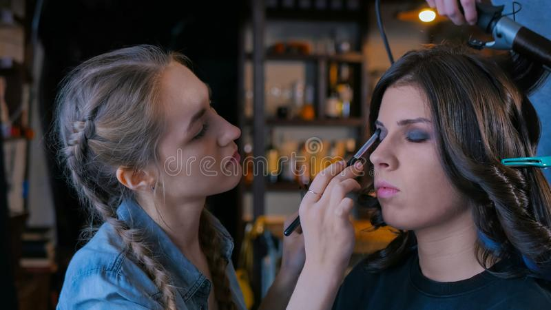 Make-up artist and hairdresser working with woman client stock image