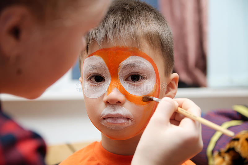 Make up artist making tiger mask for child.Children face painting. Boy painted as tiger or ferocious lion. Preparing for theatrical performance. Boy actor royalty free stock photography