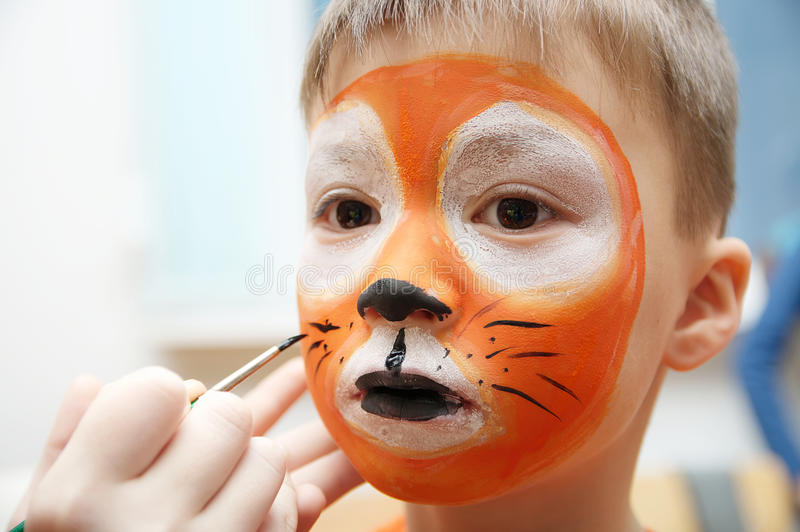 Make up artist making tiger mask for child.Children face painting. Boy painted as tiger or ferocious lion. Preparing for theatrical performance. Boy actor stock photography