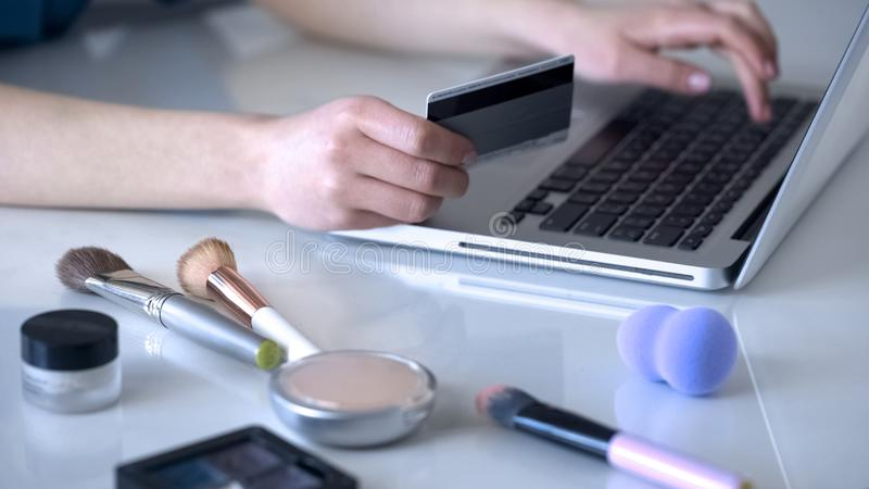 Make-up artist ordering new cosmetics online, typing data of her credit card stock photo