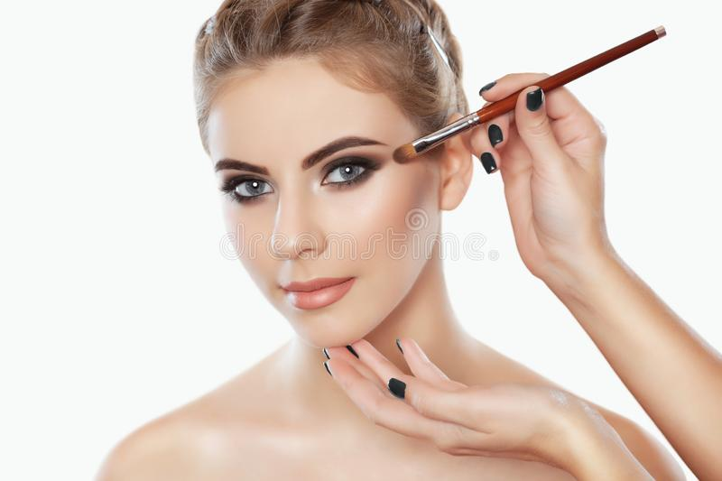 The make-up artist paints eyebrows and eyes to a beautiful girl. Applying make-up and face care stock images