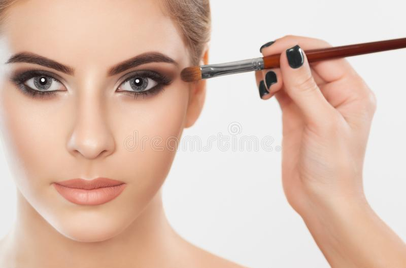 The make-up artist paints eyebrows and eyes to a beautiful girl. Applying make-up and face care stock photo
