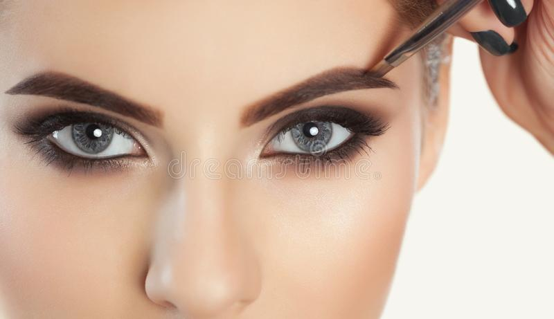 The make-up artist paints eyebrows to a beautiful girl royalty free stock photography