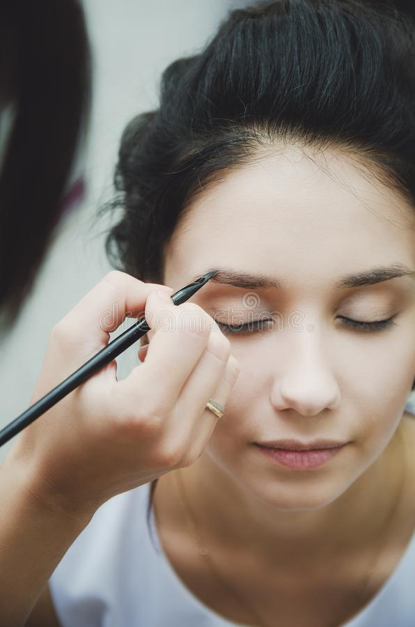 Make-up artist paints eyebrows to girl brunette, close-up royalty free stock photography