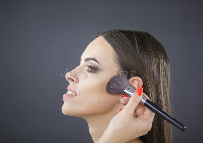 The make-up artist put the blush on the girl`s face. stock photo
