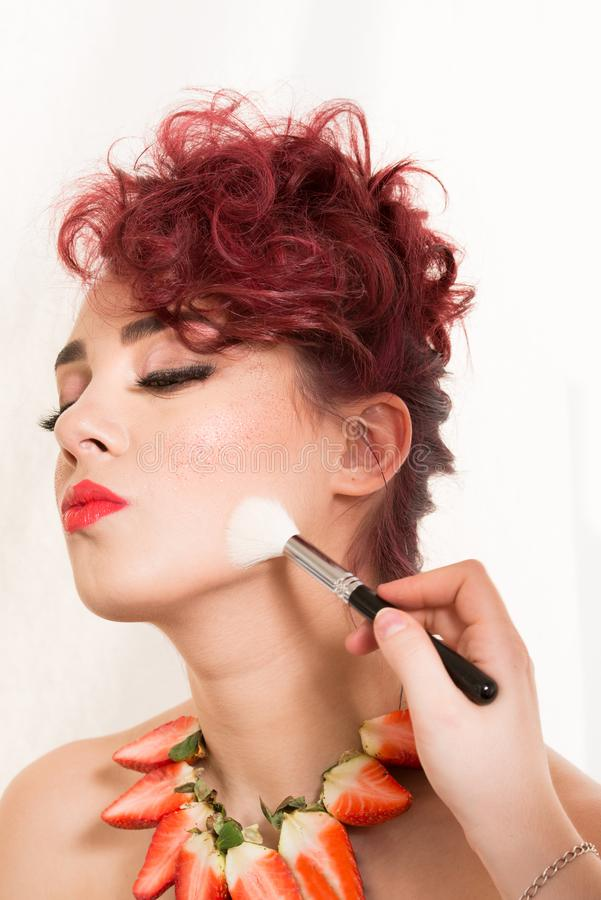 Make-up artist retouching female model`s cheek with powder brush. On white background. The model is a Caucasian redhead woman with a strawberry necklace royalty free stock photos
