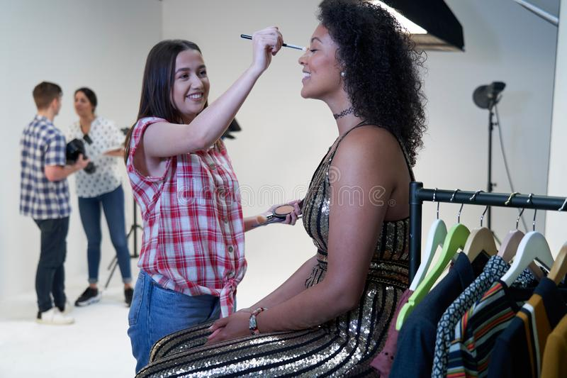 Make Up Artist Working On Fashion Shoot In Photographers Studio. Make Up Artist Works On Fashion Shoot In Photographers Studio stock image