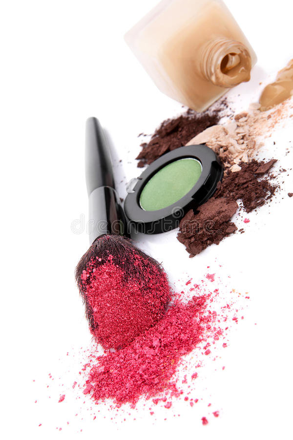 Make up background. Pink make up powder on make up brush, ground beige and brown make up and foundation on white background. Feminine beauty concept stock image