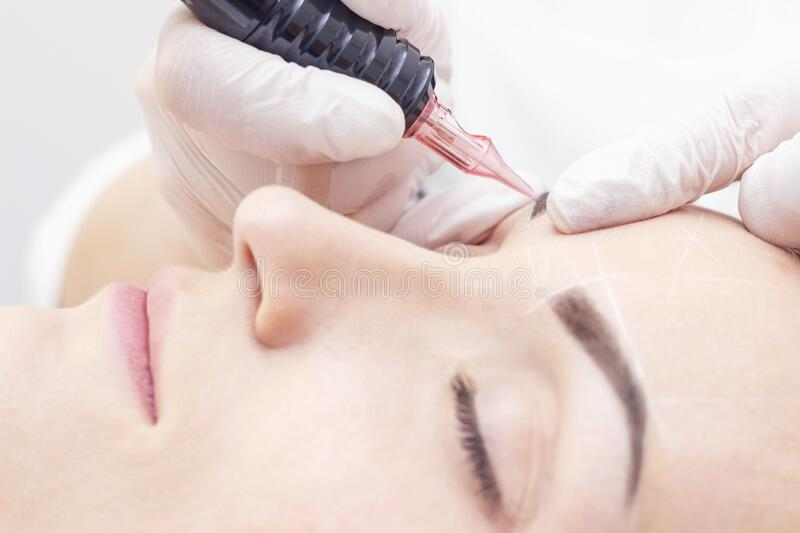 Make-Up. Beautician Hands Doing Eyebrow Tattoo On Woman Face.Permanent Brow Makeup In Beauty Salon. Closeup Of Specialist Doing Ey. Ebrow Tattooing For Female royalty free stock photography