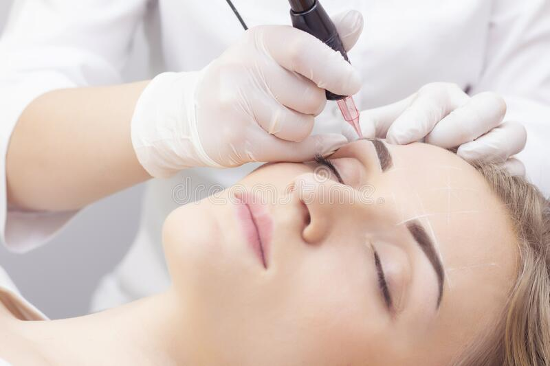 Make-Up. Beautician Hands Doing Eyebrow Tattoo On Woman Face.Permanent Brow Makeup In Beauty Salon. Closeup Of Specialist Doing Ey. Ebrow Tattooing For Female stock photo