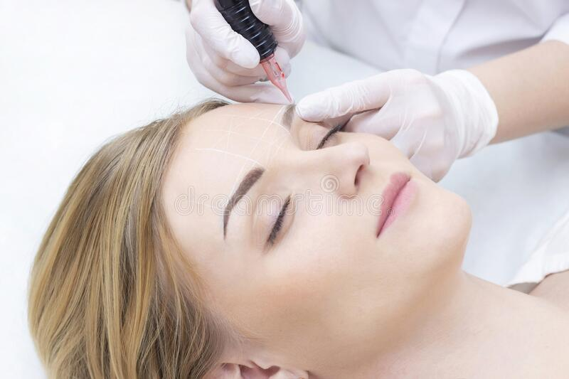Make-Up. Beautician Hands Doing Eyebrow Tattoo On Woman Face.Permanent Brow Makeup In Beauty Salon. Closeup Of Specialist Doing Ey. Ebrow Tattooing For Female stock photography