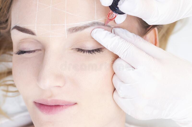 Make-Up. Beautician Hands Doing Eyebrow Tattoo On Woman Face.Permanent Brow Makeup In Beauty Salon. Vertical photo. Cosmetology Treatment stock image