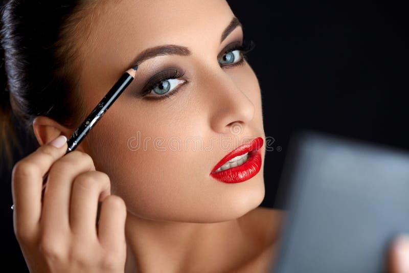 Make-up. Beautiful Woman Doing Makeup Eyebrow Pencil. Red Lips.  royalty free stock photography