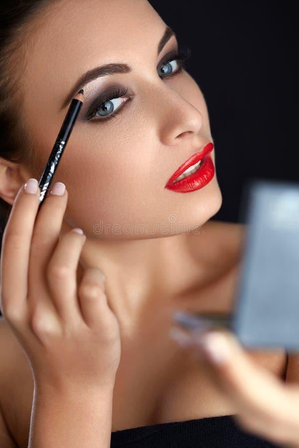 Make-up. Beautiful Woman Doing Makeup. Eyebrow Pencil. Red Lips.  stock images