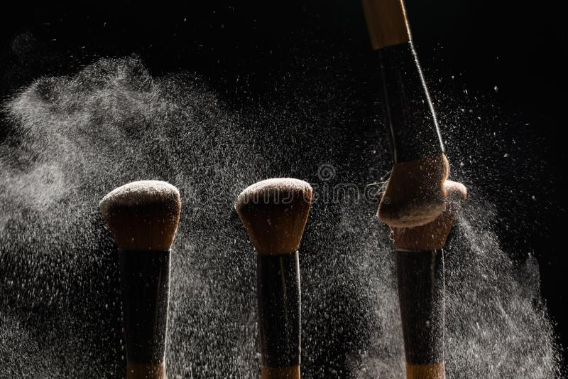 Make up, beauty and mineral cosmetics concept - Brush brushing away a powder from another brush on dark background.  stock photo