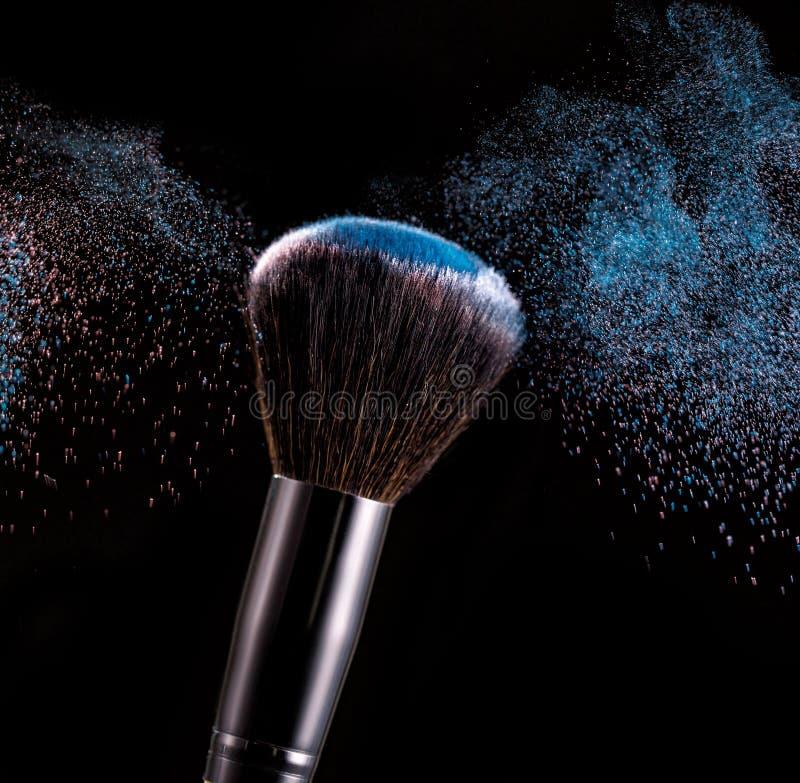 Make up brush with powder splashes on black background. Make up brush with blue powder splashes on black background. pink powder explosion royalty free stock photo